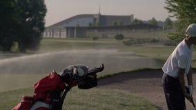Счастливый игрок в гольф мальчика Жизнерадостный младший мальчик на поле для гольфа на заходе солнца видеоматериал