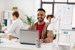 Счастливый индийский человек с портативным компьютером на офисе Стоковые Изображения RF