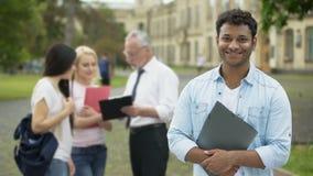 Счастливый испанский студент стоя близко коллеж и смотря в камеру, образование акции видеоматериалы