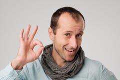 Счастливый испанский человек показывает О'КЕЫ против серой предпосылки Стоковые Изображения