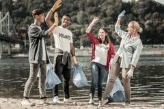 Счастливый испускать лучи вызывается добровольцем дающ максимум 5 друг к другу после завершать задачи стоковые фотографии rf