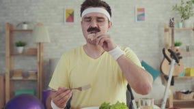 Счастливый и радостный молодой sporty человек с усиком есть овощи сидя на таблице акции видеоматериалы
