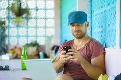 Счастливый и уверенный человек backpacker работая с ноутбуком и мобильным телефоном outdoors ослабленными как успешное независимо стоковые изображения