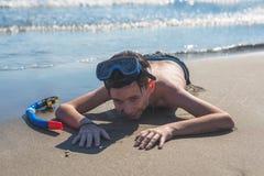 Счастливый и усмехаясь мальчик в маске и трубка на песке на пляже стоковое фото