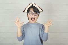 Счастливый и усмехаясь ребенок с книгой на голове стоковые фотографии rf