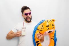 Счастливый и эмоциональный парень держит рот раскрыл whinkles nad Он держит matrass детей и стекло молока Изолировано на белизне стоковые изображения