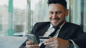 Счастливый кавказский бизнесмен в официально одеждах оплачивая онлайн счет держа кредитную карточку и smartphone в его руках внут видеоматериал
