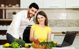 Счастливый кашевар пар с компьтер-книжкой Стоковое Фото