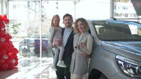 Счастливый клиент семьи в автосалоне, портрете усмехаясь родителей с меньшей девушкой ребенка на руках показывает ключи к видеоматериал