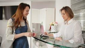Счастливый клиент womann оплачивая с кредитной карточкой в выставочном зале моды Маленькая девочка оплачивает для ее деталей сток-видео
