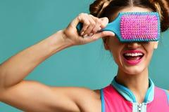 Счастливый конец женщины брюнет моды наблюдает с красочной розовой голубой большой щеткой гребня волос Стоковое Фото