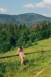 Счастливый красивый битник девушки идя на предпосылку изумительных облаков и гор неба в лете Стоковые Фото