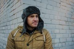 Счастливый красивый молодой человек в крышке с earflaps Молодой человек в меховой шапке стоковое фото