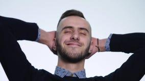Счастливый красивый молодой человек усмехаясь и кладя его руки за его изолированной головой, на белую предпосылку сток-видео