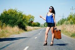 Счастливый красивый путешественник с чемоданом на дороге, заминка девушки Стоковая Фотография RF