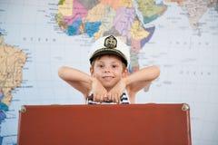Счастливый красивый ребенк в шляпе капитана с тяжелым чемоданом на предпосылке карты мира стоковые фото