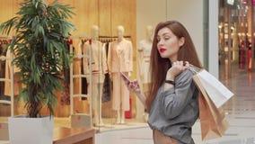 Счастливый красивый усмехаться женщины, смотря прочь, используя умный телефон на торговом центре сток-видео