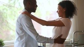Счастливый ласковый Афро-американский молодой выпуск облигаций пар обнимая в кухне видеоматериал