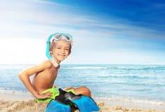 Счастливый маленький водолаз сидя на песчаном пляже стоковое изображение rf