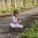 Счастливый маленький младенец играя пока сидящ на дороге в парке стоковое изображение
