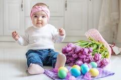 Счастливый маленький младенец сидя на поле с пасхальными яйцами Concep Стоковое Изображение RF