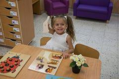 Счастливый маленький ребенок, прелестная белокурая девушка малыша, имеющ потеху играя с частями мозаики собирая sitt изображения  Стоковые Изображения RF
