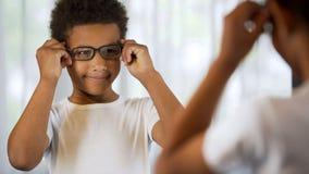 Счастливый маленький ребенок пробуя на eyeglasses, смотря в зеркале удовлетворял хорошее зрение стоковые изображения rf