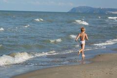 Счастливый мальчик бежать далеко вдоль пляжа моря Стоковое Изображение RF
