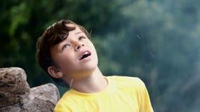 Счастливый мальчик в желтой футболке улавливает дождевые капли на природе Дым от огня на пикнике Поход, туризм и семья сток-видео