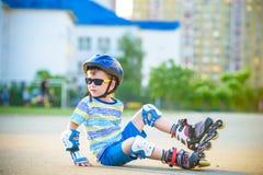 Счастливый мальчик в защитном шлеме и защитные пусковые площадки для кататься на коньках ролика   стоковая фотография rf