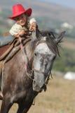 Счастливый мальчик в лошади riding шлема ковбоя outdoors Стоковые Фотографии RF