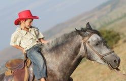 Счастливый мальчик в лошади riding шлема ковбоя outdoors Стоковые Изображения RF