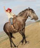 Счастливый мальчик в лошади riding шлема ковбоя outdoors Стоковая Фотография RF