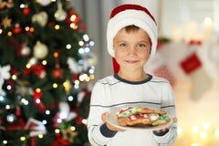 Счастливый мальчик в шляпе Санты держа плиту с печеньями дома Стоковая Фотография