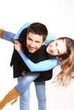 Счастливый мальчик давая езду piggyback девушки против яркой предпосылки Стоковое фото RF
