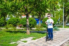 Счастливый мальчик едет скутер на дороге в парке стоковое изображение