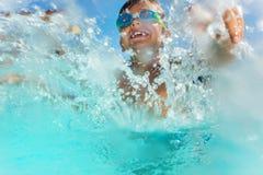 Счастливый мальчик имея потеху брызгая воду в бассейне Стоковое Фото