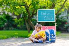 Счастливый мальчик маленького ребенка со стеклами сидя столом и рюкзаком или satchel стоковая фотография