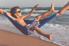 Счастливый мальчик ослабляя на пляже на времени дня Стоковая Фотография