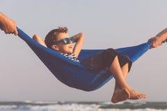 Счастливый мальчик ослабляя на пляже на времени дня Стоковые Фотографии RF