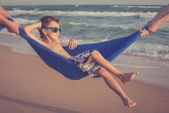 Счастливый мальчик ослабляя на пляже на времени дня Стоковое Изображение