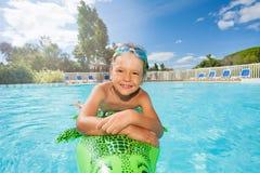 Счастливый мальчик ослабляя на раздувной игрушке в бассейне Стоковые Фотографии RF