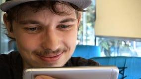 Счастливый мальчик подростка используя smartphone на современной кофейне, он ch стоковое изображение