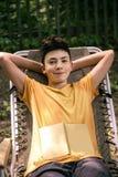 Счастливый мальчик подростка с улыбкой книги на стуле Стоковое фото RF