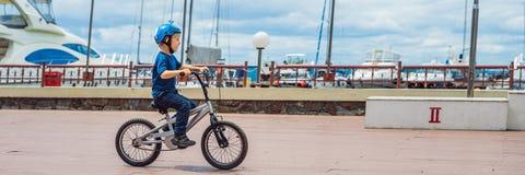 Счастливый мальчик ребенк имея потеху около яхт-клуба с велосипедом на красивый день ЗНАМЯ шлема велосипеда активного ребенка нос стоковое фото rf