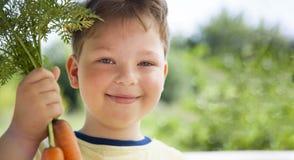 Счастливый мальчик сдерживая морковь, ребенка a с овощем Ребенк есть свежие морковей стоковая фотография rf