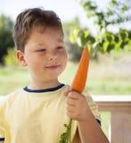 Счастливый мальчик сдерживая морковь, ребенка a с овощем Eatin ребенк стоковое изображение