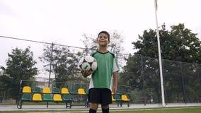 Счастливый мальчик смотря к камере пока держащ футбольный мяч акции видеоматериалы