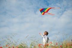 Счастливый мальчик стоя среди поля цветка держа красочный змея Стоковые Изображения RF