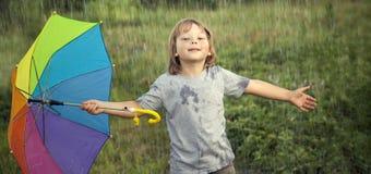 Счастливый мальчик с зонтиком outdoors, ребенок с зонтиком идет I стоковое фото